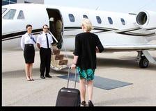 Passagerare som hälsas av piloten och stewardessen Arkivbild