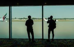 Passagerare som håller ögonen på flygplan på flygplatsen royaltyfria bilder