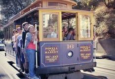 Passagerare som rider kabelbilen i San Francisco Arkivfoto