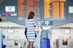 Passagerare som ser informationsbrädet om flyg arkivfoton