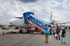 Passagerare som skriver in ett Lion Air flygplan på Soekarno-Hatta den internationella flygplatsen Fotografering för Bildbyråer
