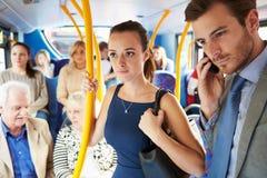 Passagerare som står på den upptagna pendlarebussen Arkivfoto