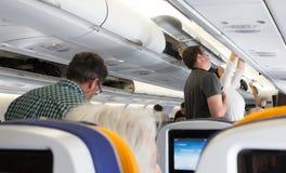 Passagerare som tar deras bagage från det över huvudet rummet Royaltyfria Bilder