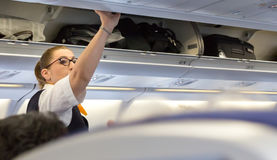 Passagerare som tar deras bagage från det över huvudet rummet Royaltyfri Fotografi