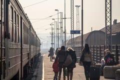 Passagerare som väntar för att stiga ombord ett drev på plattformen av Belgrade den huvudsakliga drevstationen under en solig eft arkivfoton