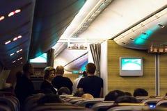 Passagerare som väntar på en toilette på ett långt flyg royaltyfri foto