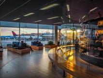 Passagerare som vilar på den Schiphol flygplatsen i thotta arkivbilder