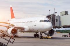 Passagerareflygplan på teletrapen på flygplatsen, service på terminalen på den tiden av päfyllning Arkivfoto