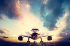 Passagerareflygplan som tar av på landningsbana på solnedgången Royaltyfri Bild