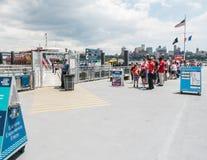 Passagerarelinje väntningar att stiga ombord sightfärjan från pir 11, Ea Royaltyfria Bilder