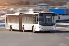 Passageraren förlängde den artikulerade bussstadsbussen av vita färgritter på den hög hastigheten längs huvudvägen royaltyfri foto