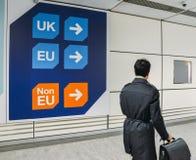 Passageraren går förbi tecken före invandringkontrollpasserande ett tecken som pekar in mot köer för UK, EU och Icke-EU Royaltyfri Fotografi