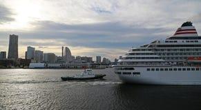 Passagerareskepp och bogserbåten som navigerar en port Royaltyfria Bilder