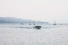Passagerarfärja på en sjö med segelbåtar Royaltyfri Fotografi