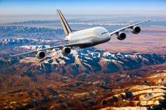 Passagerarflygplan i flykten över berglandskapet royaltyfri fotografi