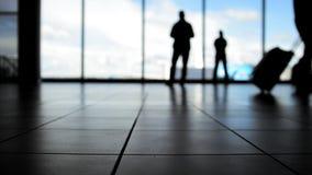 Passagers allant à l'embarquement avec des bagages devant la fenêtre dans l'aéroport, silhouette clips vidéos