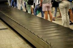 Passagers attendant à la bande de conveyeur de bagage d'aéroport Photos stock