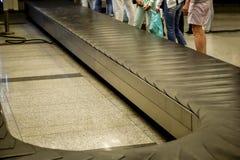 Passagers attendant à la bande de conveyeur de bagage d'aéroport Image libre de droits
