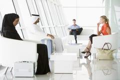 Passagers attendant dans le salon de déviation d'aéroport Photo libre de droits