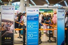 Passagers au comptoir d'enregistrement malaisien de lignes aériennes, aéroport international de Kuala Lumpur, Malaisie Photo libre de droits