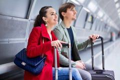 Passagers avec du charme avec le train de attente de bagage Images libres de droits