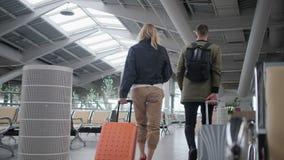 Passagers d'aéroport roulant leur bagage banque de vidéos
