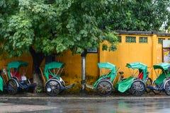 Passagers de attente de Cyclos au jour pluvieux en Hoi An, Vietnam Photos stock