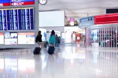 Passagers de marche avec des bagages dans l'aéroport Photographie stock libre de droits