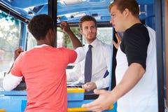 Passagers discutant avec le chauffeur de bus Photo stock