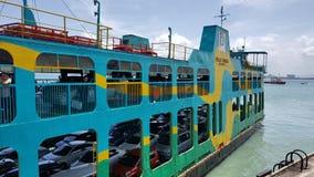 Passagers et leurs voitures utilisant le ferry public photographie stock