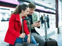 Passagers gais de sourire avec le train de attente de bagage Image stock