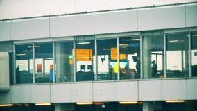 Passagers inconnus dans le salon de départ de l'aéroport international Chopin, vue de l'extérieur Varsovie, Pologne Photographie stock libre de droits