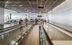 Passagers sur un passage couvert mobile dans l'aéroport Images libres de droits
