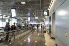Passagers sur un passage couvert mobile dans l'aéroport Image libre de droits