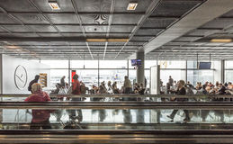 Passagers sur un passage couvert mobile et à une porte dans l'aéroport Photos stock