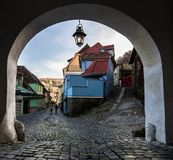 Passageway under an arch in the old city. Pass under an arch in the old city of Sighisoara. In the autumn afternoon on the small streets paved with a cobble Royalty Free Stock Images