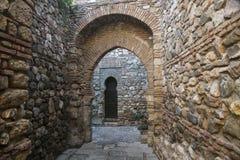 Passaggio di pietra nascosto nella fortezza di Malaga con i archs ed il portone Immagine Stock Libera da Diritti