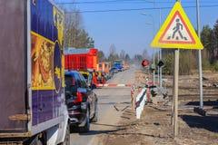 Passaggio a livello chiuso giri del treno, automobili che aspettano l'apertura della barriera infiammando un semaforo immagini stock libere da diritti