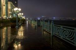 Passaggio pedonale bagnato del lato del porto allineato con le lampade Fotografia Stock