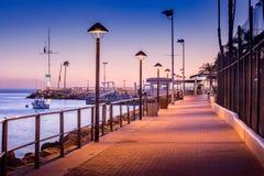 Passaggio pedonale del mattone al bacino della barca alla luce in anticipo di alba, streelights sopra, ombre, quiete, pacifico ca Immagine Stock