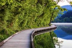 Passaggio pedonale di legno intorno al lago sanguinato con le montagne e le case sui precedenti Bella natura slovena Sanguinata,  fotografia stock libera da diritti