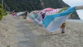 Passaggio pedonale lungo i parapetti di legno sulla spiaggia con gli asciugamani di spiaggia d'ondeggiamento con i postumi della  stock footage