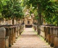 Passaggio pedonale pavimentato di pietra della laterite con le poste di pietra indipendenti ai portoni del tempio khmer antico co immagini stock libere da diritti