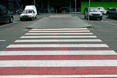 Passaggio pedonale su una strada asfaltata davanti ad una costruzione di parcheggio Fotografia Stock