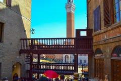 Passaggio stretto fra le case a Piazza del Campo con Palazzo P immagini stock