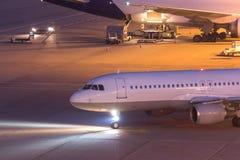Passagier aiplane, das einen Flughafen nachts weitergeht Lizenzfreies Stockbild