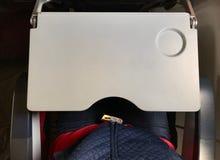 Passagier, der Blue Jeans trägt, befestigt roten Sicherheitsgurt in der Flugzeugkabine Lizenzfreies Stockbild