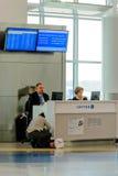 Passagier, der von einem Fluglinienvertreter an einem modernen a sich erkundigt Lizenzfreies Stockbild