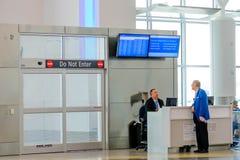 Passagier, der von einem Fluglinienvertreter an einem modernen a sich erkundigt Lizenzfreie Stockbilder