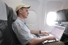 Passagier met laptop in vliegtuig stock foto